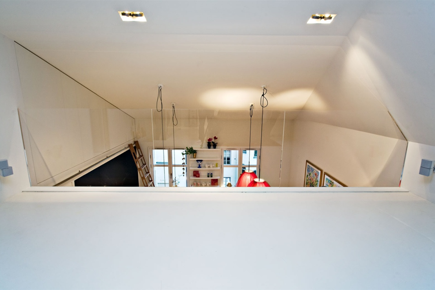 A view from the loft towards the kitchen is clean and white.
