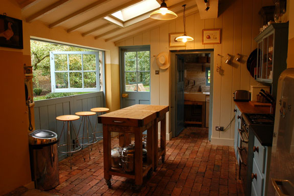 The kitchen area is centered by a rustic wooden island, while a coveted spot along the windows is lined with barstools. I'd love to eat my morning meal staring at the view.
