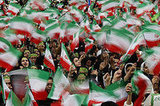 Iranian schoolgirls wave Iranian flags during the rally.