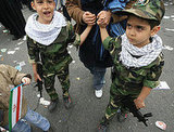 Iranian children wearing military fatigues and holding toy guns take part in a rally.