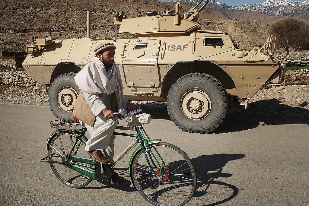 A man rides a bicycle past a US Army military vehicle on patrol.