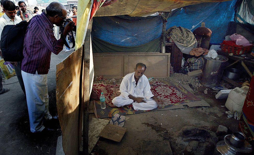 A photojournalist takes pictures through a hole in the shanty of Slumdog Millionaire child actor Mohammed Azharuddin's father Mohammed Ismail in Mumbai.