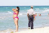 People enjoy the beach while a policeman patrols