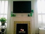 Let's face it, a lot of us have flat screens hanging over our mantels these days. So if you need a place to keep your cable box, use your fireplace. Just top it with some candles or flowers to kick the commercial vibe. Source