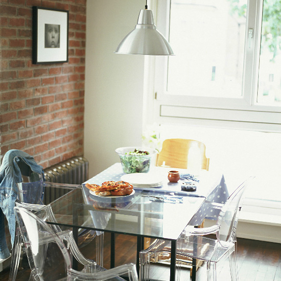 In this small contemporary dining room, Louis Ghost chairs reflect light and enhance the space, facing off with the industrial quality of exposed brick and a steel pendant light. Source