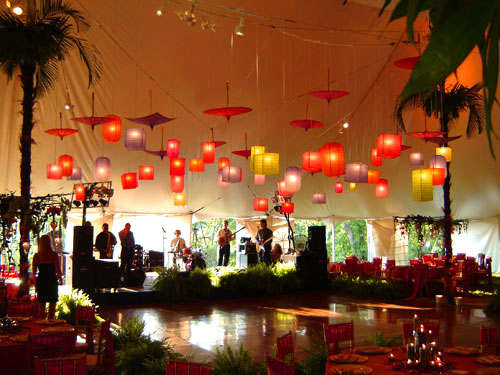 Create visual interest by mixing shapes and colors. Here, jewel-toned rectangular paper lanterns and hanging parasols draw the eye toward the tent canopy. Source