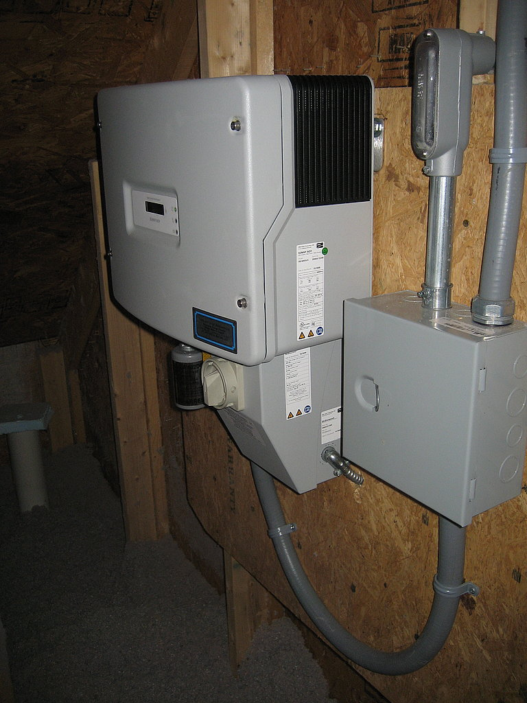 The inverter converts DC power from the solar panels into the AC power needed for powering the appliances in the home.