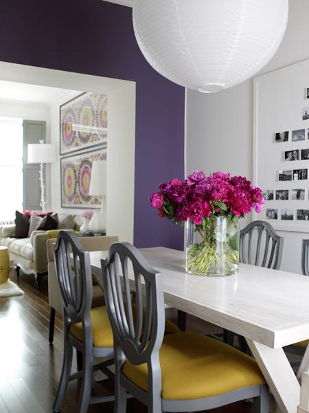 Walker used a single plum accent wall to create a cohesive palette between the two rooms. And an inexpensive paper lantern lends drama to this dining room thanks to its large size.