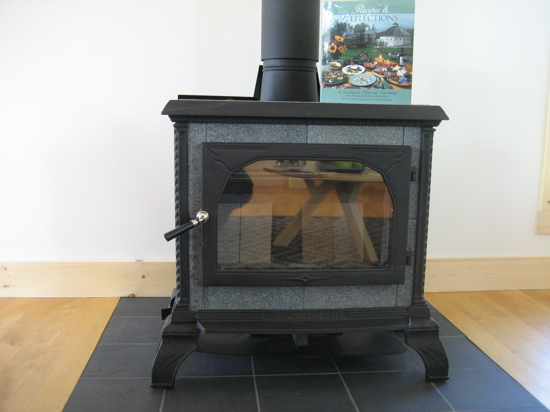 A woodburning stove keeps the living room cozy on chilly evenings.